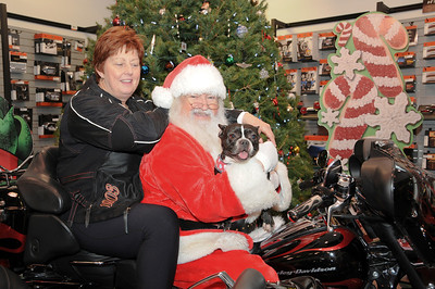 Pat Heck hopped on the back of the Harley while Santa held her Phoebe for a photo.  Hamburg, PA