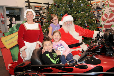 """Emily (11), Travis (9) and little sister Abby (6) have their photo taken with Santa and Mrs. Claus at Schaeffer's Harley-Davidson's annual """"Pictures with Santa"""" event. Hamburg, PA"""