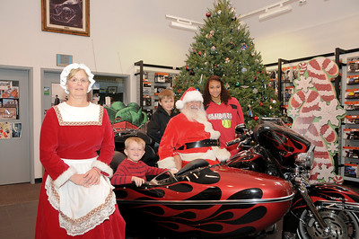 Amber (15), Tarik (12) and Gunner (6) pose for their picture with Santa and Mrs. Claus Schaeffer's Harley-Davidson this past Saturday.  Shartlesville, PA